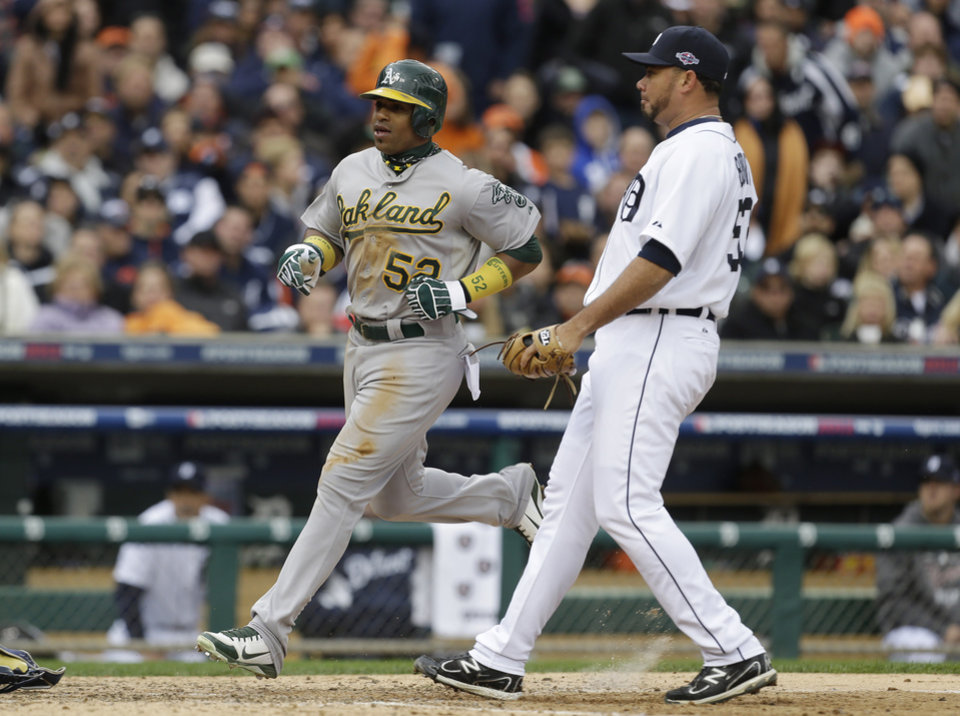 Photo -   Oakland Athletics' Yoenis Cespedes scores in front of Detroit Tigers relief pitcher Joaquin Benoit from third on a wild pitch during the eighth inning of Game 2 of the American League division baseball series, Sunday, Oct. 7, 2012, in Detroit. (AP Photo/Paul Sancya)
