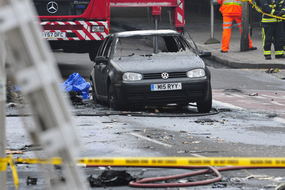 Photo - A damaged car remains in the street after a helicopter crashed into a construction crane on top of St George's Wharf tower building, in London, Wednesday Jan. 16, 2013. Police say two people were killed when a helicopter crashed during rush hour in central London after apparently hitting a construction crane on top of a building. (AP Photo/Vince Pol)