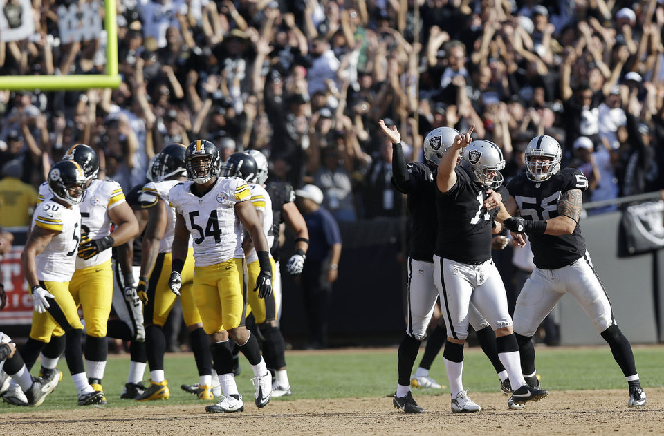 Photo -   Oakland Raiders kicker Sebastian Janikowski, second from right, celebrates with teammates Dave Tollefson, right, and holder Shane Lechler, third from right, after kicking a 43-yard game-winning field goal during the fourth quarter of an NFL football game against the Pittsburgh Steelers in Oakland, Calif., Sunday, Sept. 23, 2012. At left are Steelers linebackers Larry Foote (50) and Chris Carter (54). Oakland won 34-31. (AP Photo/Marcio Jose Sanchez)