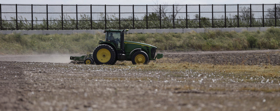 Photo -   In this Sept. 6, 2012, photo, a tractor is used to farm in cotton field along a border fence that passes through the property in Brownsville, Texas. Since 2008, hundreds of landowners on the U.S.-Mexico border have sought fair prices for property that was condemned to make way for the fence, but many of them received initial offers that were far below market value. (AP Photo/Eric Gay)