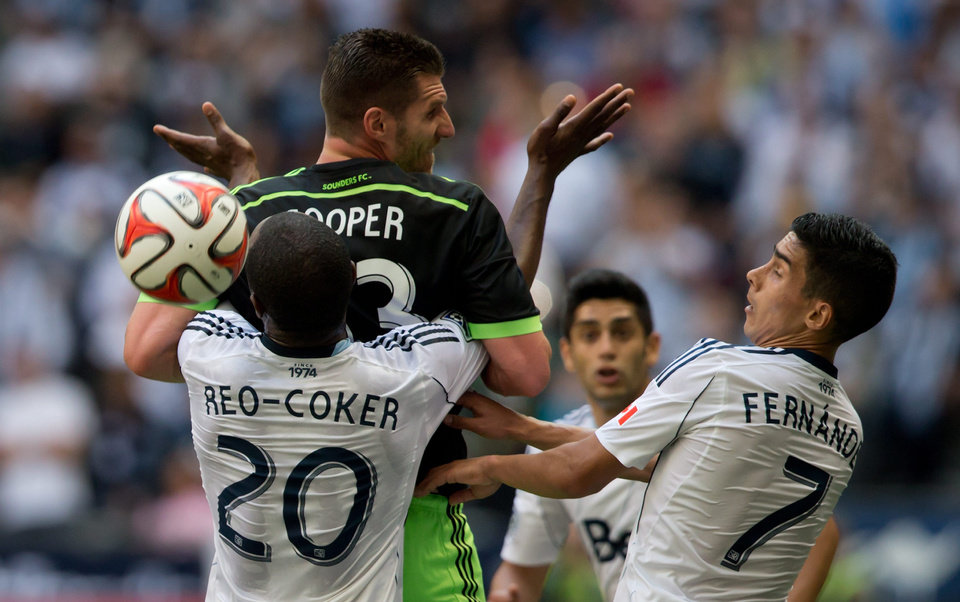 Photo - Seattle Sounders' Kenny Cooper, top left, is tied up by Vancouver Whitecaps' Nigel Reo-Coker, of England, (20) on a throw-in as Whitecaps' Sebastian Fernandez, of Uruguay, (7) watches during the first half of an MLS soccer game in Vancouver, British Columbia, Saturday, May 24, 2014. (AP Photo/The Canadian Press, Darryl Dyck)