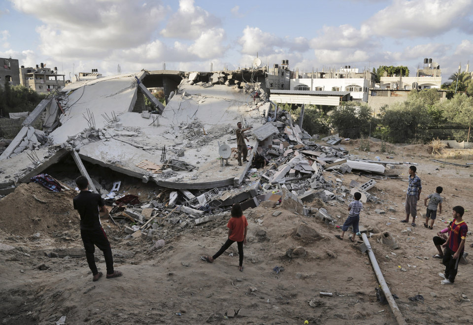 Photo - Palestinians inspect the rubble of a destroyed building after it was hit by an Israeli airstrike in Beit Lahiya, northern Gaza Strip, Tuesday, July 15, 2014. The Israeli military says it has resumed airstrikes on Gaza after Hamas militants violated a de-escalation brokered by Egypt. (AP Photo/Adel Hana)
