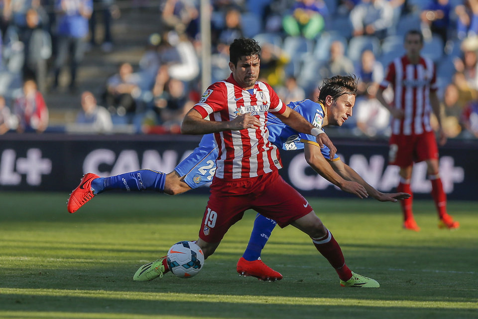 Photo - Atletico's Diego Costa, left, in action with Getafe's Mosquera, during a Spanish La Liga soccer match between Getafe and Atletico Madrid at the Coliseum Alfonso Perez  stadium in Madrid, Spain, Sunday, April 13, 2014. (AP Photo/Andres Kudacki)