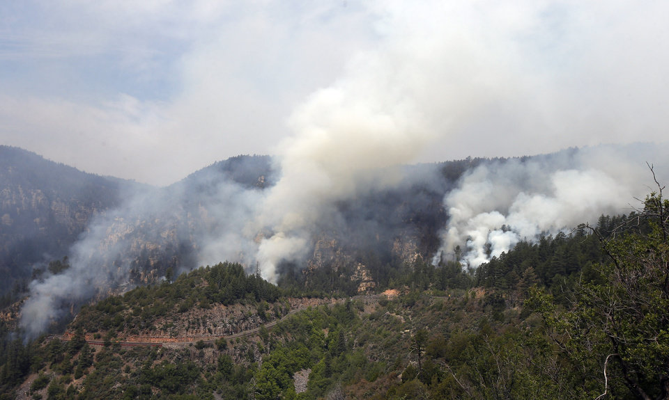 Photo - Smoke plumes from several spots along the Slide Fire heads skyward as the fire burns up Oak Creek Canyon on Friday, May 23, 2014, near Flagstaff, Ariz.  The fire has burned approximately 7,500 acres and is five percent contained. (AP Photo/Ross D. Franklin)
