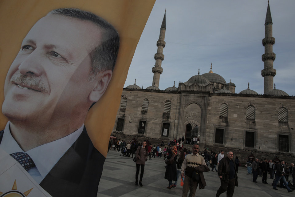 Photo - A poster of Turkish Prime Minister Recep Tayyip Erdogan is seen in an election billboard of his Justice and Development Party with a mosque in the background in Istanbul, Turkey, Thursday, March 27, 2014. Erdogan has been ensnared in a corruption scandal that has toppled four Cabinet ministers. He has provoked outrage at home and abroad with an attempt to block Twitter and YouTube. His incessant us-against-them rhetoric and conspiracy theories have alienated allies. Meanwhile, the Turkish Lira has fallen, interest rates are up and the Turkish economy has fallen off a cliff. It all might be enough to oust any leader. But as Turks prepare to vote in local elections Sunday, it's all about Erdogan.(AP Photo/Emrah Gurel)