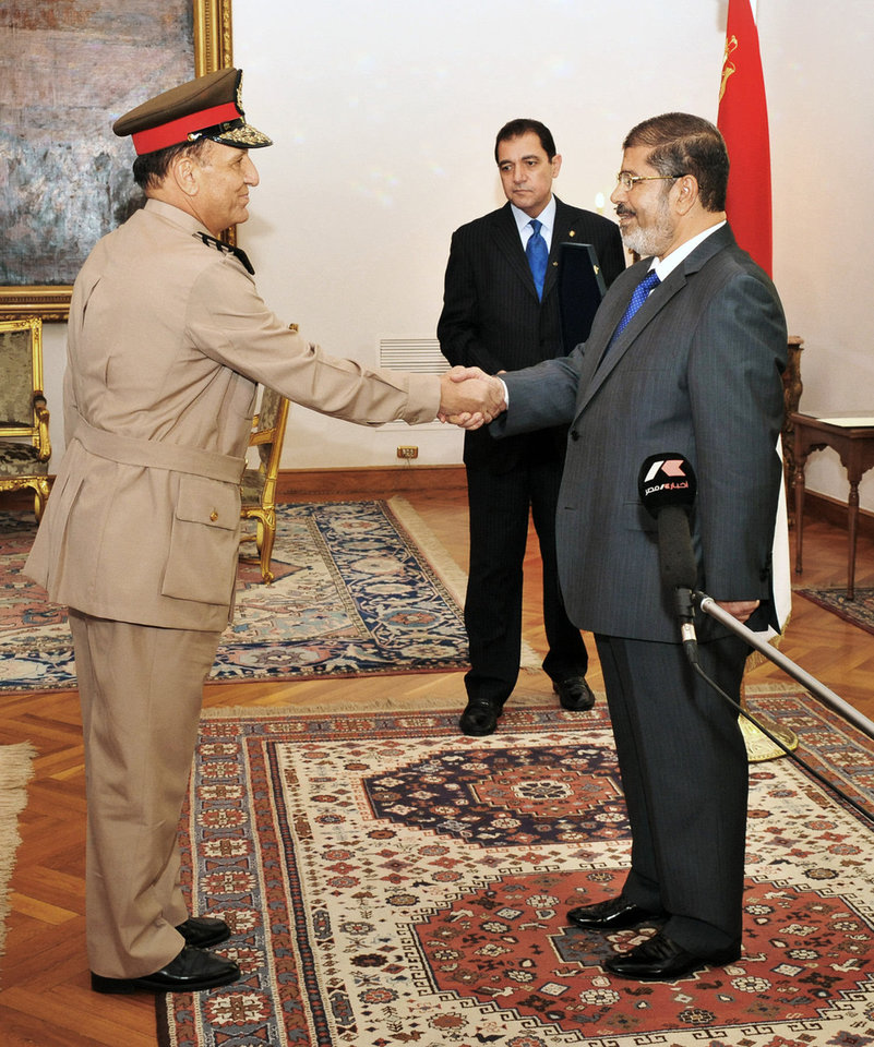 Photo - In this photo released by Middle East News Agency, former Armed Forces Chief of Staff Sami Anan, left, shakes hands with Egyptian President Mohammed Morsi at the Presidential Palace in Cairo, Egypt, Tuesday, Aug. 14, 2012. AP photo  Uncredited