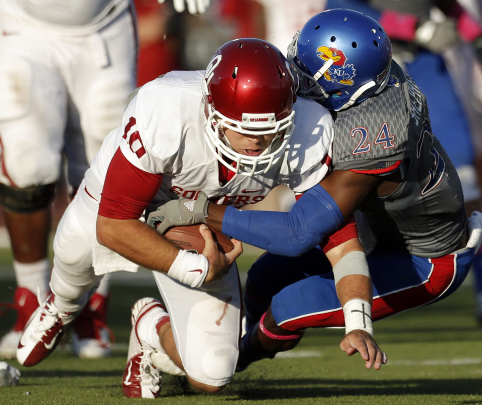 OU's Blake Bell (10) is tackled by KU's JaCorey Shepherd (24) in the fourth quarter during of the college football game between the University of Oklahoma Sooners (OU) and the University of Kansas Jayhawks (KU) at Memorial Stadium in Lawrence, Kan., Saturday, Oct. 19, 2013. OU won 34-19. Photo by Sarah Phipps, The Oklahoman