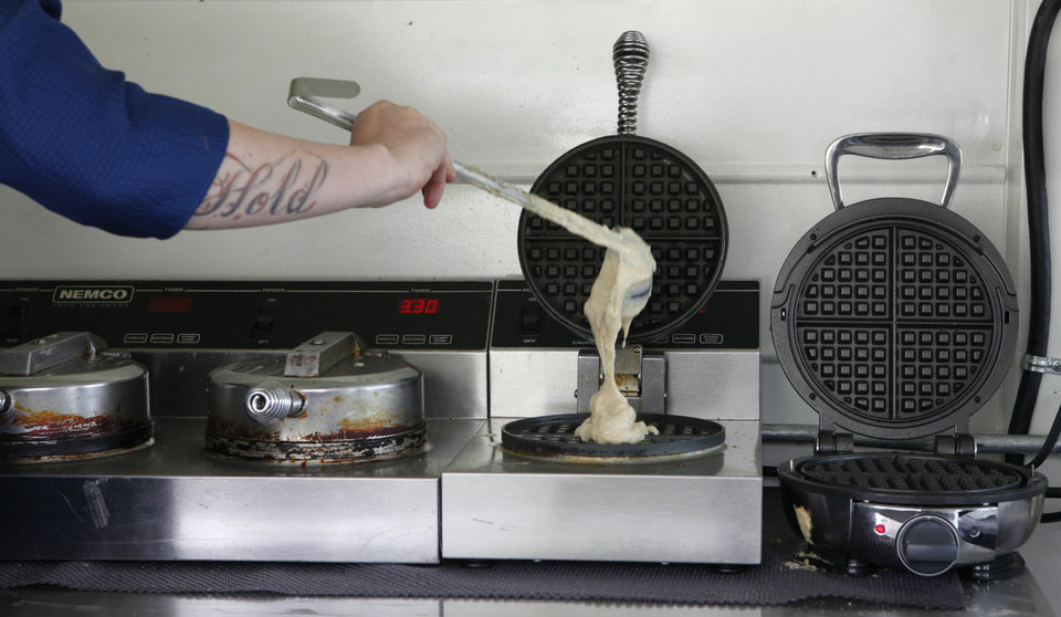 Tara Taylor pours batter in a waffle iron in the Waffle Champion truck in Oklahoma City. <strong>David McDaniel - The Oklahoman</strong>