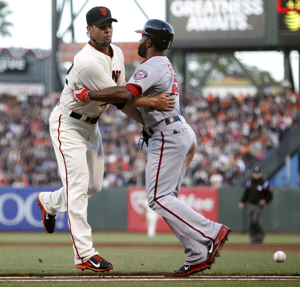 Photo - San Francisco Giants pitcher Ryan Vogelsong, left, collides with Washington Nationals' Denard Span after Span hit a short ball down the first base line during the second inning of a baseball game, Monday, June 9, 2014, in San Francisco, Calif. (AP Photo/Beck Diefenbach)