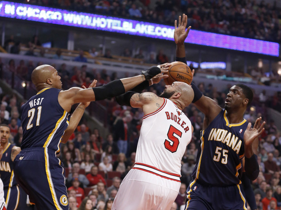 Photo - Indiana Pacers forward David West (21) and Roy Hibbert (55) pressure Chicago Bulls forward Carlos Boozer (5) during the first half of an NBA basketball game Monday, March 24, 2014, in Chicago. (AP Photo/Charles Rex Arbogast)