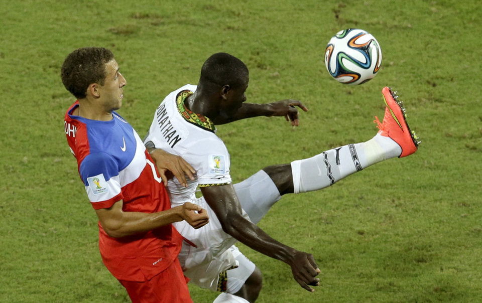 Photo - United States' Fabian Johnson, left, and Ghana's Jonathan Mensah challenge for the ball during the group G World Cup soccer match between Ghana and the United States at the Arena das Dunas in Natal, Brazil, Monday, June 16, 2014. (AP Photo/Hassan Ammar)
