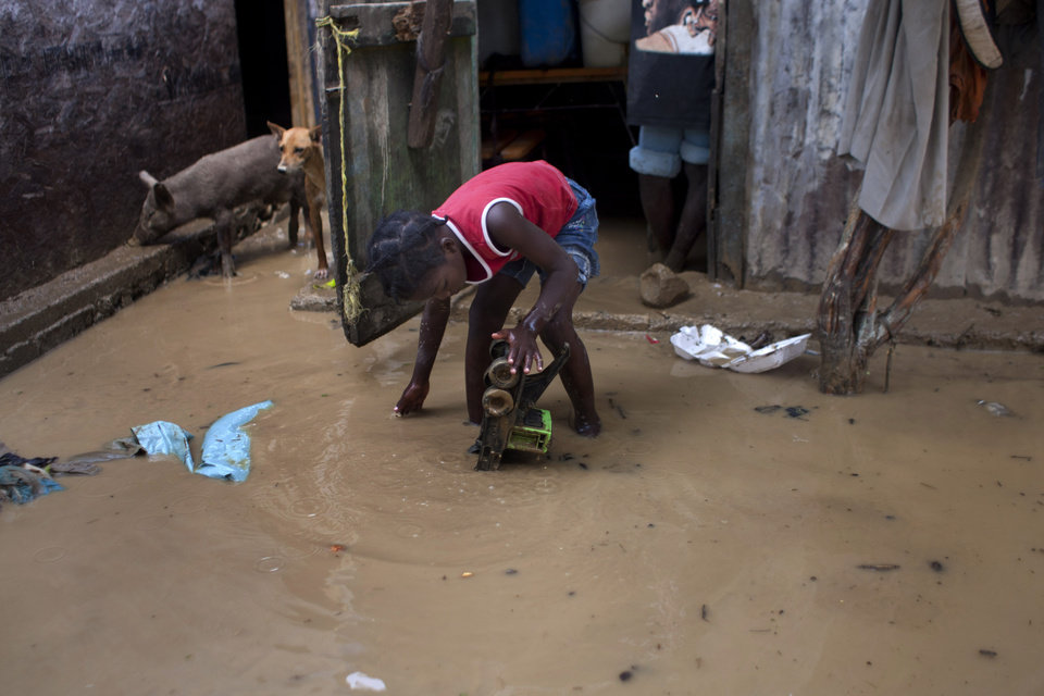 A girl recovers a toy from muddy waters at her flooded house after the passing of Tropical Storm Isaac in Port-au-Prince, Haiti, Sunday Aug. 26, 2012. The death toll in Haiti from Tropical Storm Isaac has climbed to seven after an initial report of four deaths, the Haitian government said Sunday. (AP Photo/Dieu Nalio Chery) ORG XMIT: PAP122