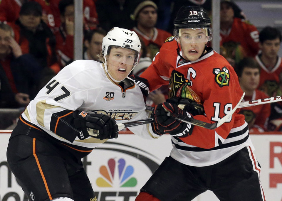 Photo - Chicago Blackhawks' Jonathan Toews, right, and Anaheim Ducks' Hampus Lindholm watch the puck during the second period of an NHL hockey game in Chicago, Friday, Jan. 17, 2014. (AP Photo/Nam Y. Huh)