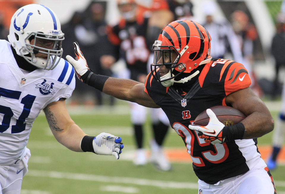 Photo - Cincinnati Bengals running back Gio Bernard (25) runs against Indianapolis Colts inside linebacker Pat Angerer (51) in the second half of an NFL football game, Sunday, Dec. 8, 2013, in Cincinnati. (AP Photo/Tom Uhlman)