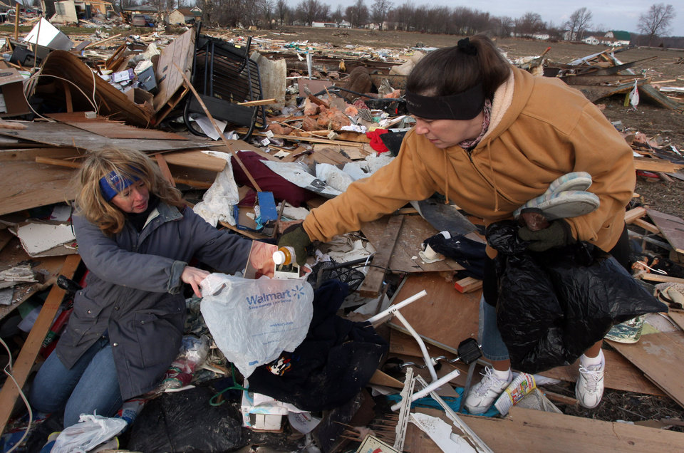 Unidentified women search through debris of Ted and Brenda Tolbert's Holton, Ind. home Sunday, March 4, 2012. A string of violent storms scratched away small towns in Indiana and cut off rural communities in Kentucky as an early-season tornado outbreak killed at least 37 people on Saturday. The Tolberts are in the hospital after their house fell on them during the storms. (AP Photo/Ernest Coleman) ORG XMIT: INEC108