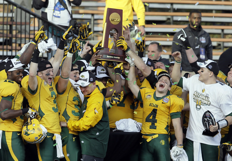 Photo - North Dakota State players celebrate with the trophy after winning the FCS championship NCAA college football game against Towson, Saturday, Jan. 4, 2014, in Frisco, Texas. NDSU won 35-7. (AP Photo/Tony Gutierrez)