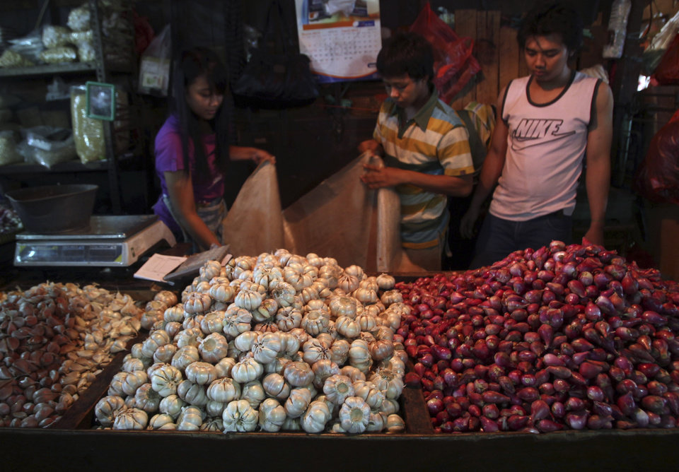 Photo - Garlic and shallots vendors wait for customers at a market in Jakarta, Indonesia, Wednesday, March 20, 2013. The price of beef, the main ingredient in bakso, has hit a record high while other essential ingredients — garlic, shallots and chillies — have also recently skyrocketed. (AP Photo/Tatan Syuflana)