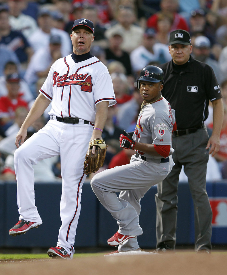 Atlanta Braves third baseman Chipper Jones, left, reacts after a throwing error during the fourth inning of the National League wild card playoff baseball game against the St. Louis Cardinals, Friday, Oct. 5, 2012, in Atlanta. (AP Photo/John Bazemore)