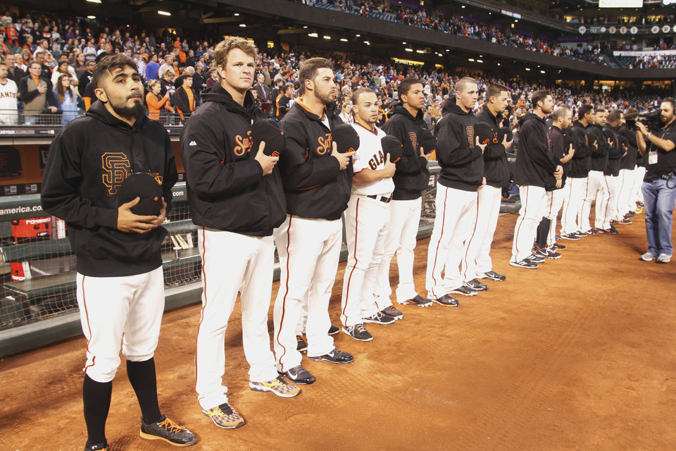 San Francisco Giants observe a moment of silence before a baseball game aganist the Los Angeles Dodgers, Thursday, Sept. 26, 2013, in San Francisco, in memory of a man who was fatally stabbed after a Dodgers-Giants game on Wednesday, not far from At&T Park. Giants' Sergio Romo, left, and Matt Cain, second from left, hold their caps. (AP Photo/George Nikitin)