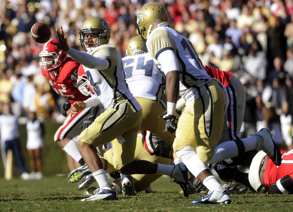 Photo - Georgia Tech quarterback Tevin Washington (13) pitches to running back Synjyn Days, right, as they run against Georgia during the second half of an NCAA college football game, Saturday, Nov. 24, 2012, in Athens, Ga. Georgia won 42-10. (AP Photo/John Amis)