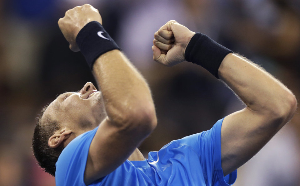 Photo -   Tomas Berdych, of the Czech Republic, raises his arms after beating Roger Federer, of Switzerland, 7-6 (1), 6-4, 3-6, 6-3 in a quarterfinal of the U.S. Open tennis tournament, Wednesday, Sept. 5, 2012, in New York. (AP Photo/Charles Krupa)