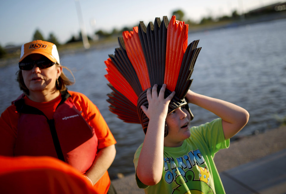 Caleb Unruh, 10, tries on a hat worn by Mary Miller, left, the drummer for Team 1:05 with the OSU Foundation during the Oklahoma Regatta Festival on the Oklahoma River in Oklahoma City, Thursday, Oct. 3, 2013. Photo by Bryan Terry, The Oklahoman