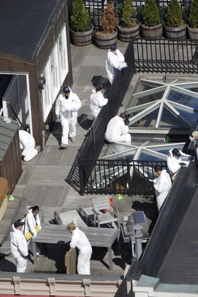Investigators inspect the roof of a building adjacent to the area where a bomb exploded near the Boston Marathon finish line, Thursday, April 18, 2013, in Boston. Investigators in white jumpsuits fanned out across the streets, rooftops and awnings around the blast site in search of clues.  (AP Photo/Julio Cortez)