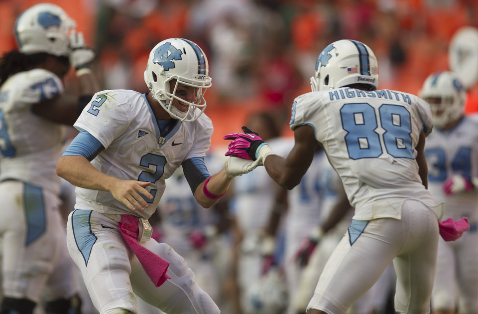 North Carolina quarterback Bryn Renner (2) and wide receiver Erik Highsmith (88) celebrate after defeating Miami during an NCAA college football game in Miami, Saturday, Oct. 13, 2012. North Carolina won 18-14. (AP Photo/J Pat Carter)