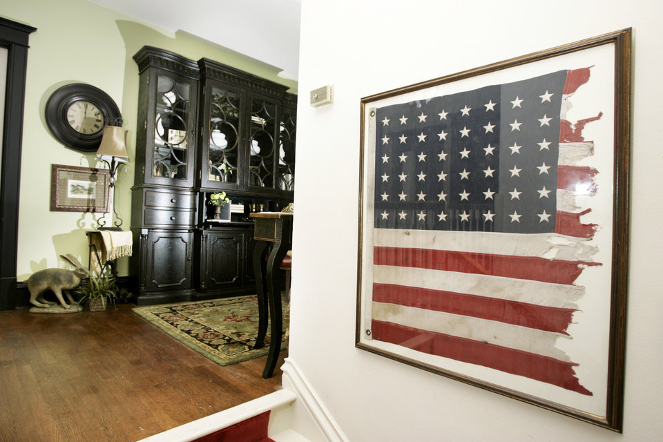 """Photo - Remnants of an American flag burned in front of the house by the Klu Klux Klan in 1923 hang at the top of the stairs of the 2009 Symphony Designers Show House, 431 NW 17. John """"Jack"""" Walton, then governor — and soon impeached — won office with support of the KKK but turned against the Klan, which retaliated by  burning a cross, which scorched the flag on a nearby pole.PHOTO BY STEVE GOOCH, THE OKLAHOMAN"""