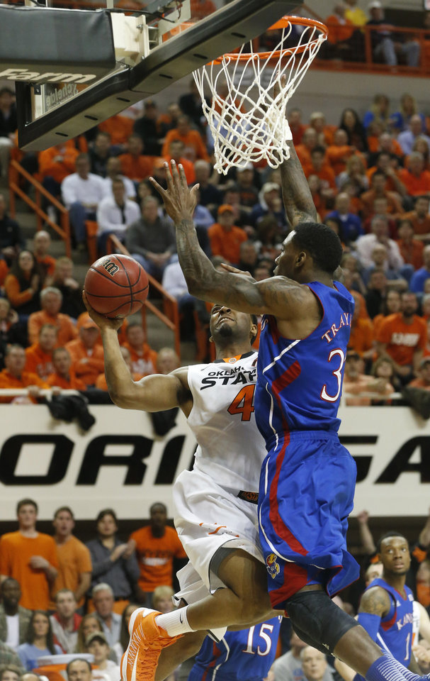 Photo - Oklahoma State guard Brian Williams (4) shoots as Kansas forward Jamari Traylor (31) defends during the first half of an NCAA college basketball game in Stillwater, Okla., Wednesday, Feb. 20, 2013. (AP Photo/Sue Ogrocki)