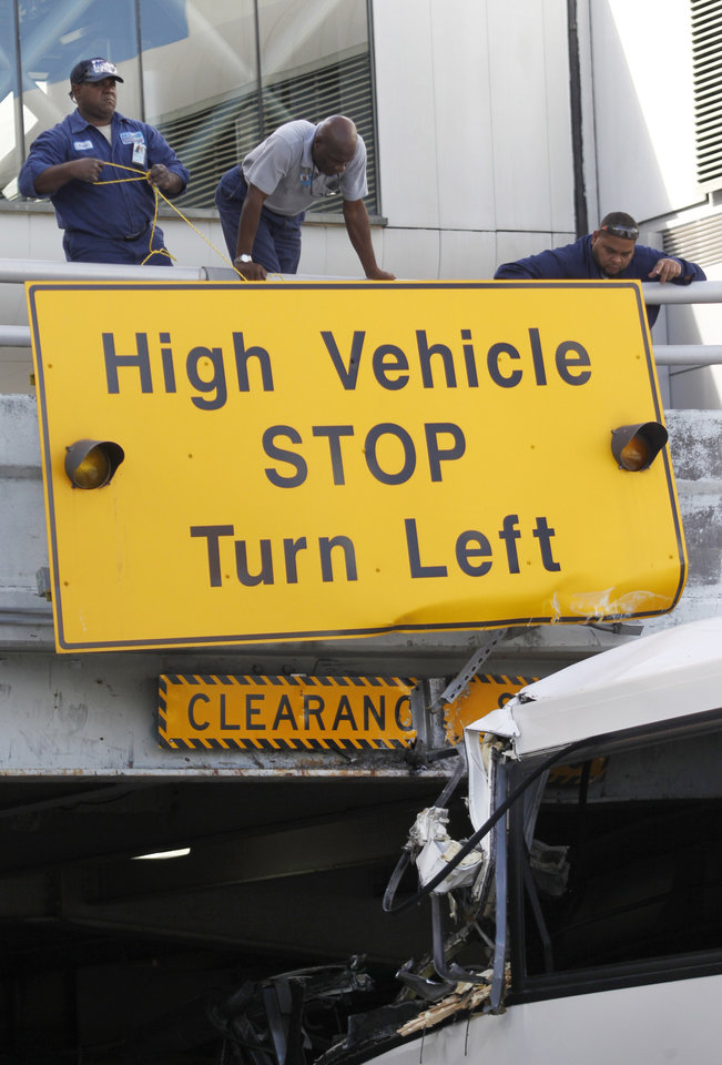 Photo - Airport workers secure a sign after a bus hit a concrete overpass at Miami International Airport in Miami on Saturday, Dec. 1, 2012. The vehicle was too tall for the 8-foot-6-inch entrance to the arrivals area, and buses are supposed to go through the departures area which has a higher ceiling, according to an airport spokesperson. (AP Photo/Wilfredo Lee)