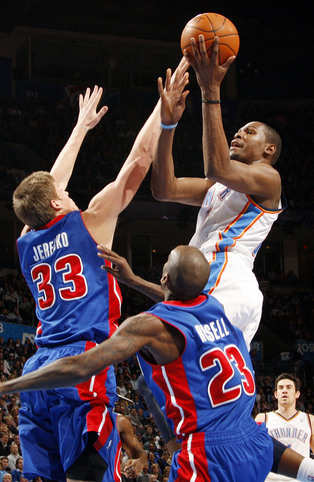 Photo - Oklahoma City's Kevin Durant (35) shoots the ball over Jonas Jerebko (33) and Walker Russell (23) of Detroit during the NBA basketball game between the Detroit Pistons and Oklahoma City Thunder at the Chesapeake Energy Arena in Oklahoma City, Monday, Jan. 23, 2012. Photo by Nate Billings, The Oklahoman