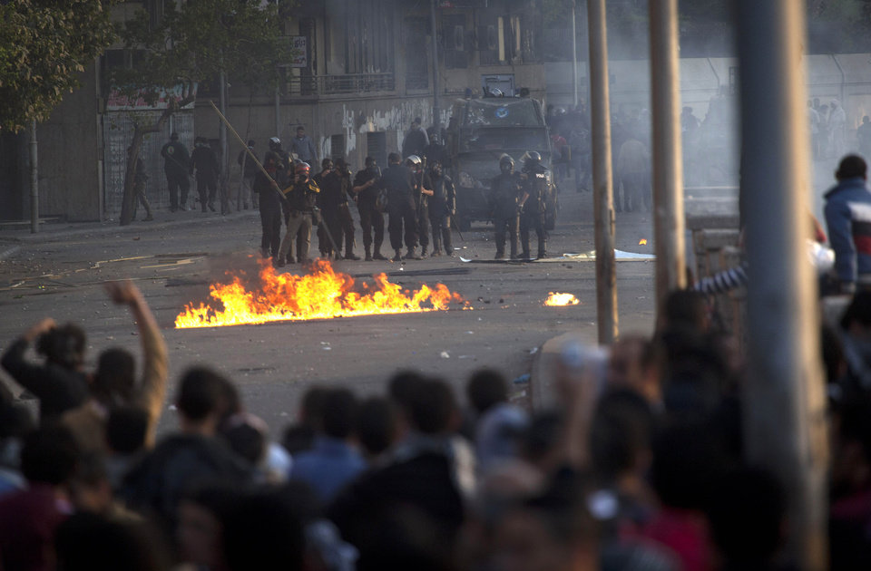 Photo - Egyptian protesters clash with riot police in downtown Cairo, Egypt, Saturday, March 9, 2013. Security officials say a protester has died during clashes between police and hundreds of stone-throwing demonstrators in central Cairo. The officials say the protester died Saturday on a Nile-side road where clashes have been taking place daily between anti-government protesters and police near two luxury hotels and the U.S. and British embassies. (AP Photo/Nasser Nasser)