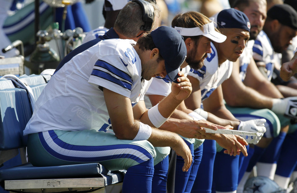 Photo -   Dallas Cowboys quarterback Tony Romo, left, sits on the bench after being sacked in the second half of an NFL football game against the Seattle Seahawks, Sunday, Sept. 16, 2012, in Seattle. (AP Photo/John Froschauer)
