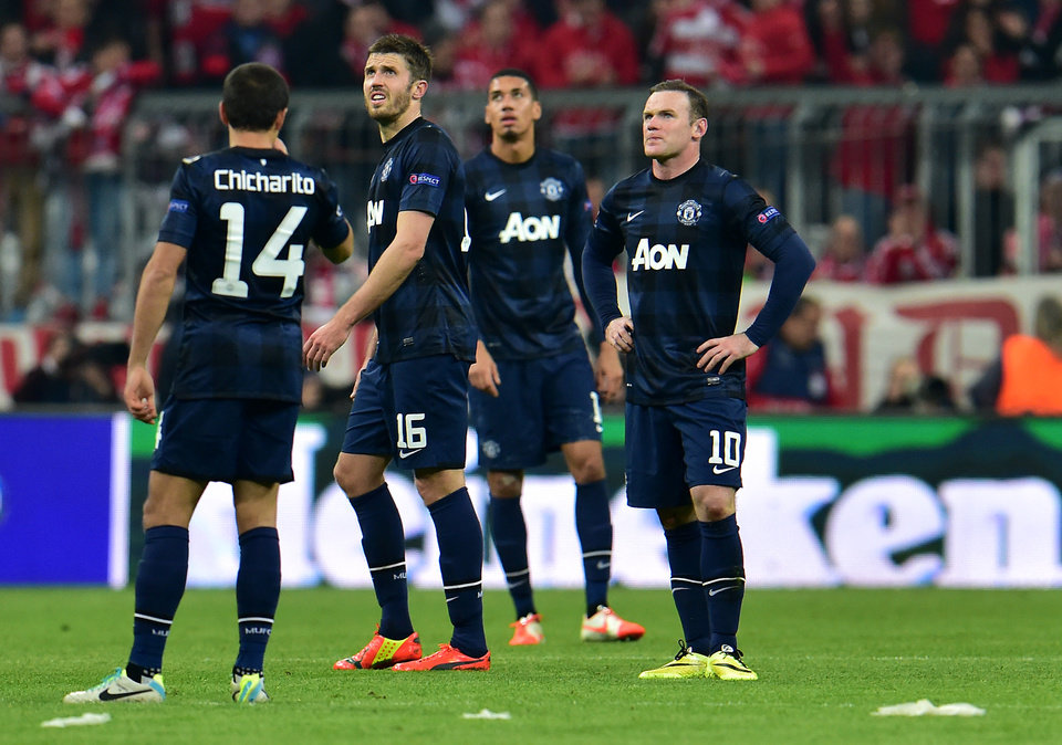 Photo - Manchester United's Wayne Rooney, right, looks on after Munich scored the third goal during the Champions League quarterfinal second leg soccer match between Bayern Munich and Manchester United in the Allianz Arena in Munich, Germany, Wednesday, April 9, 2014. (AP Photo/Kerstin Joensson)