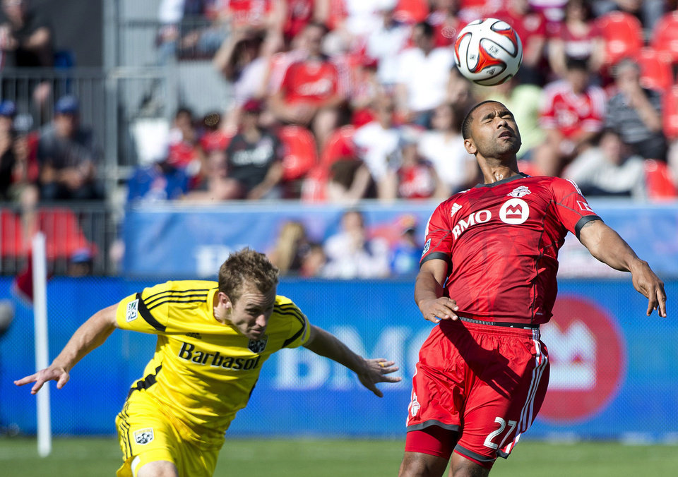 Photo - Toronto FC forward Luke Moore, right, heads the ball past Columbus Crew defender Tyson Wahl during the first half of an MLS soccer game in Toronto on Saturday, May 31, 2014. (AP Photo/The Canadian Press, Nathan Denette)