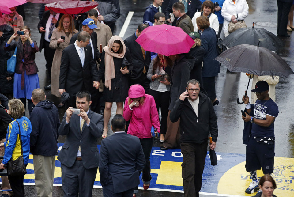 Photo - Family members, survivors and friends of the 2013 Boston Marathon bombing react near the finish line after a remembrance ceremony on Boylston Street in Boston, Tuesday, April 15, 2014. (AP Photo/Elise Amendola)