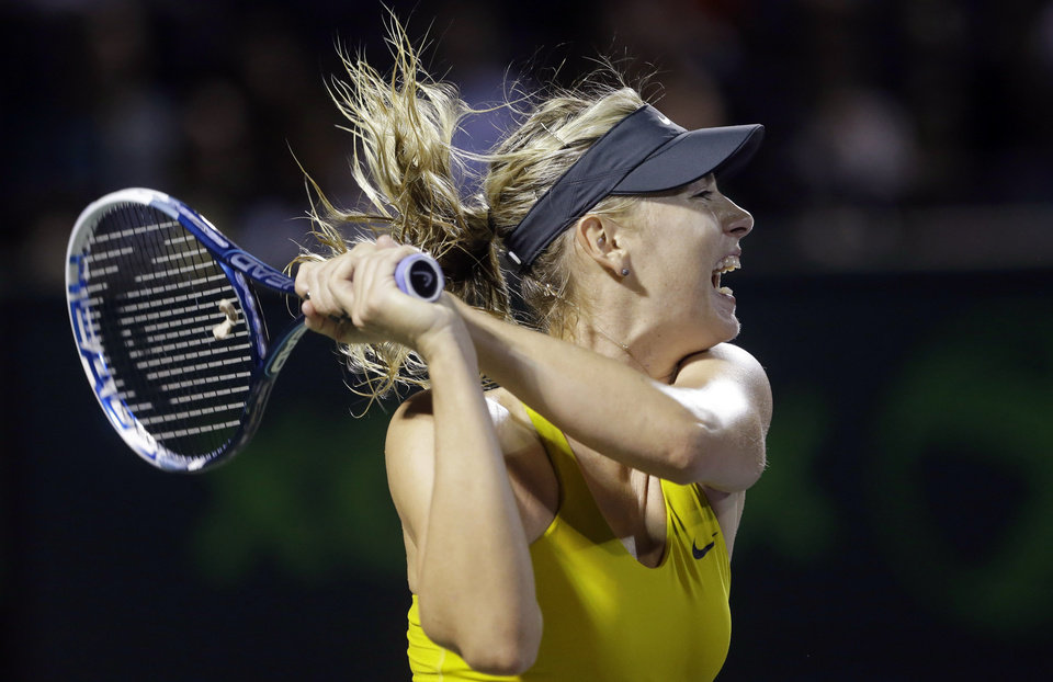 Photo - Maria Sharapova, of Russia, returns a shot from Lucie Safarova, of the The Czech Republic, at the Sony Open tennis tournament, Saturday, March 22, 2014, in Key Biscayne, Fla. (AP Photo/Wilfredo Lee)