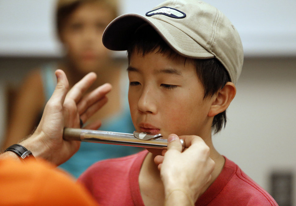 Photo - Above: Tao Zhu, a Whittier Middle School student, tries out the flute during an instrument fair at Norman High School on Saturday.