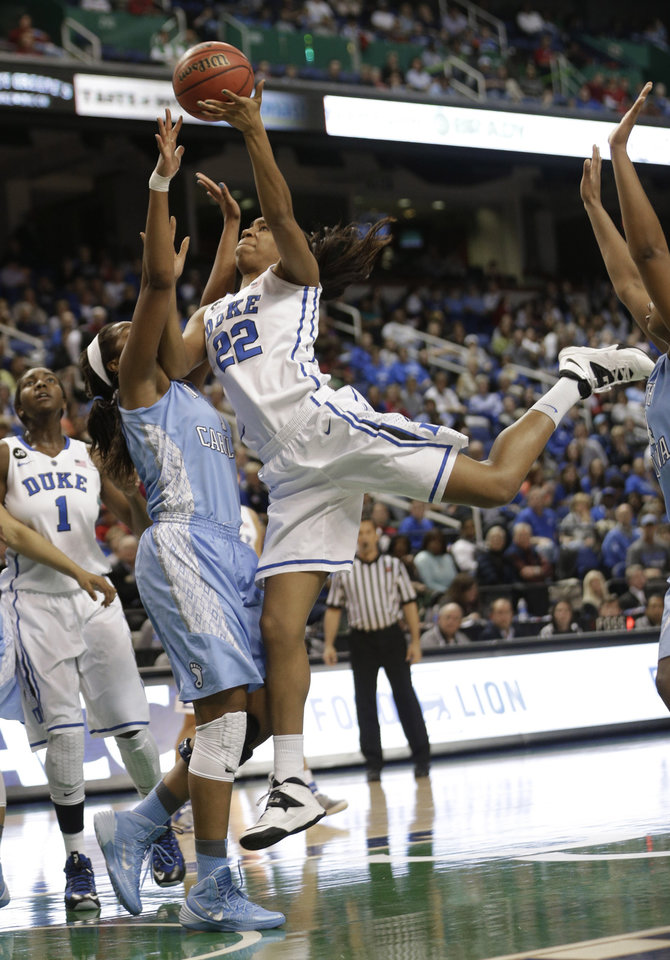 Photo - Duke's Oderah Chidom, right, tries to shoot over North Carolina's Brittany Rountree, left, during the first half of an NCAA college basketball semi-final game at the Atlantic Coast Conference tournament in Greensboro, N.C., Saturday, March 8, 2014. (AP Photo/Chuck Burton)