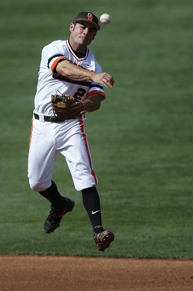 Photo - Oklahoma State's Tim Arakawa (2) makes a throw to first during the bedlam matchup between the University of Oklahoma and Oklahoma State University in the Phillips 66 Big 12 Baseball Championship in Oklahoma City, Okla. on Wednesday, May 21, 2014.   Photo by Chris Landsberger, The Oklahoman
