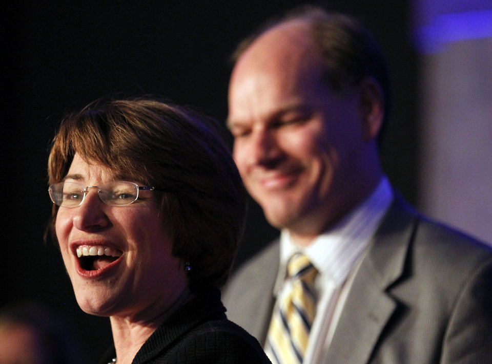 Photo -   U.S. Senator Amy Klobuchar, D-Minn., speaks at an election night event accompanied by husband John Bessler, right, at the Crowne Plaza, Tuesday, Nov. 6, 2012, in St. Paul, Minn. (AP Photo/The Star Tribune, Carlos Gonzalez) MANDATORY CREDIT; ST. PAUL PIONEER PRESS OUT; MAGS OUT; TWIN CITIES TV OUT