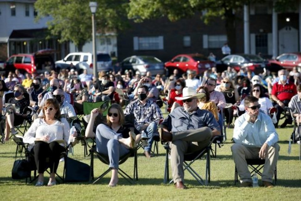 Photo -  People watch graduation ceremonies while spread out on the south lawn at OBU. [Sarah Phipps/The Oklahoman]