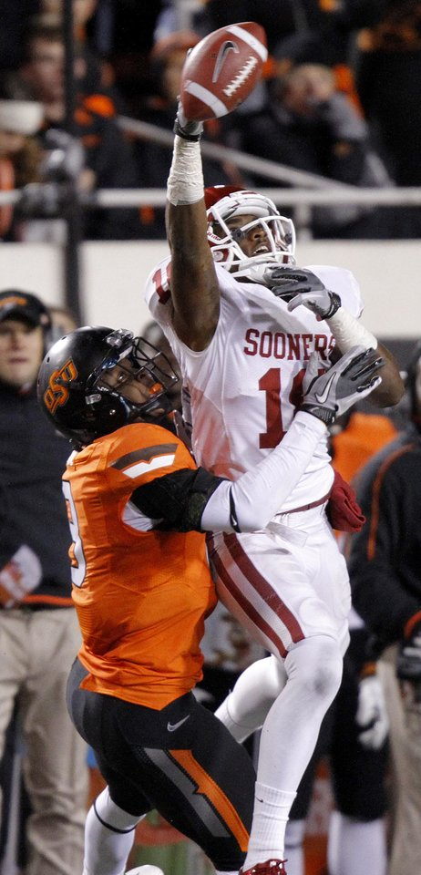 Photo - Oklahoma State's Daytawion Lowe (8) breaks up a pass for Oklahoma's Kameel Jackson (18) during the Bedlam college football game between the Oklahoma State University Cowboys (OSU) and the University of Oklahoma Sooners (OU) at Boone Pickens Stadium in Stillwater, Okla., Saturday, Dec. 3, 2011. Photo by Chris Landsberger, The Oklahoman