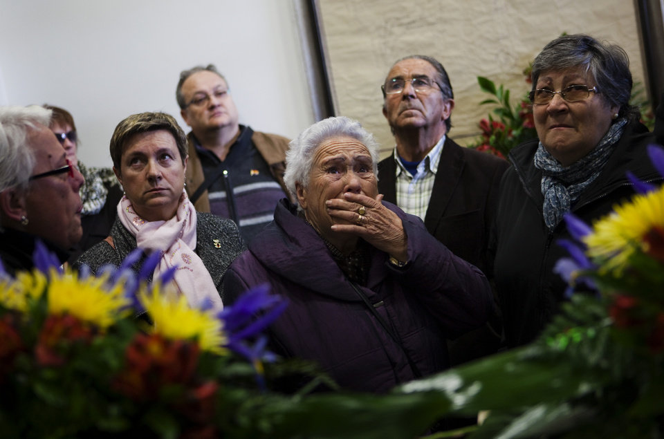 Relatives and neighbors react during the funeral of four people found in an unmarked dump dating from the country's civil war, in Torrellas, Zaragoza, Saturday, April 14, 2012. Pilar Perez, who presides over the town council of Torrellas, says the bodies were discovered and exhumed in October 2010. DNA analysis revealed they were those of former mayor Gregorio Torres and residents Luis Torres, Feliciano Lapuente and Marcelino Navarro. All four had been driven out of town and shot by forces loyal to Gen. Francisco Franco in 1936 after the beginning of the war, which lasted until 1939. Relatives and around 200 residents attended a ceremony at the town hall on Saturday before a formal burial in the town's cemetery. (AP Photo/Emilio Morenatti)