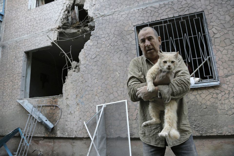 Photo - Valery who gave only his first name carries his suffered cat in front of his damaged house after shelling in the city of Slovyansk, Donetsk Region, eastern Ukraine Monday, June 30, 2014. Residential areas came under shelling on Monday morning from government forces. (AP Photo/Dmitry Lovetsky)