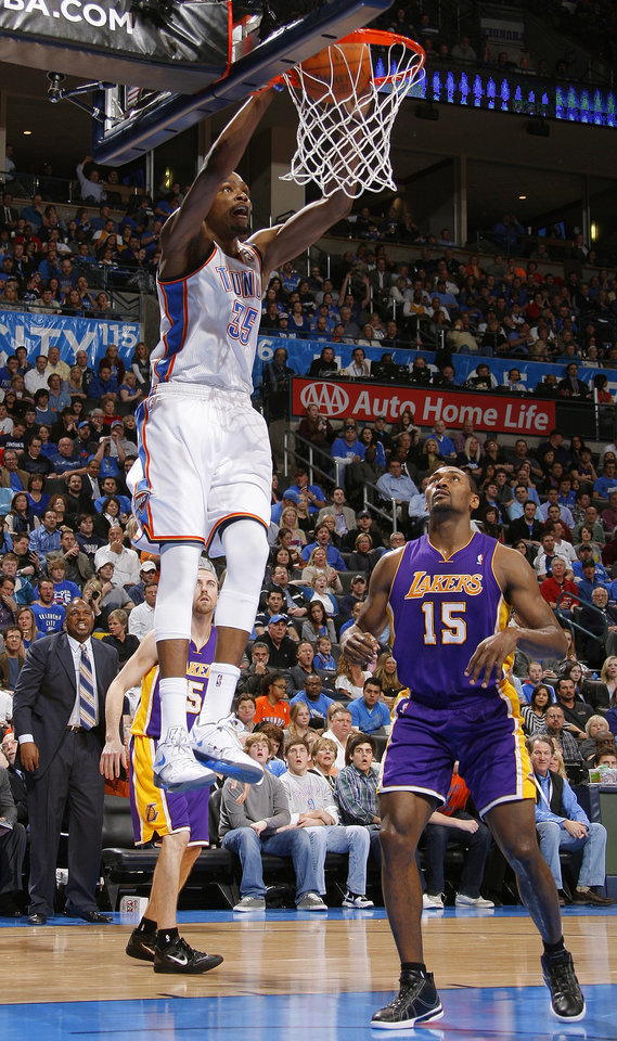 Photo - Oklahoma City's Kevin Durant (35) dunks the ball beside Los Angeles' Metta World Peace (15) during an NBA basketball game between the Oklahoma City Thunder and the Los Angeles Lakers at Chesapeake Energy Arena in Oklahoma City, Thursday, Feb. 23, 2012.  Oklahoma City won 100-85. Photo by Bryan Terry, The Oklahoman