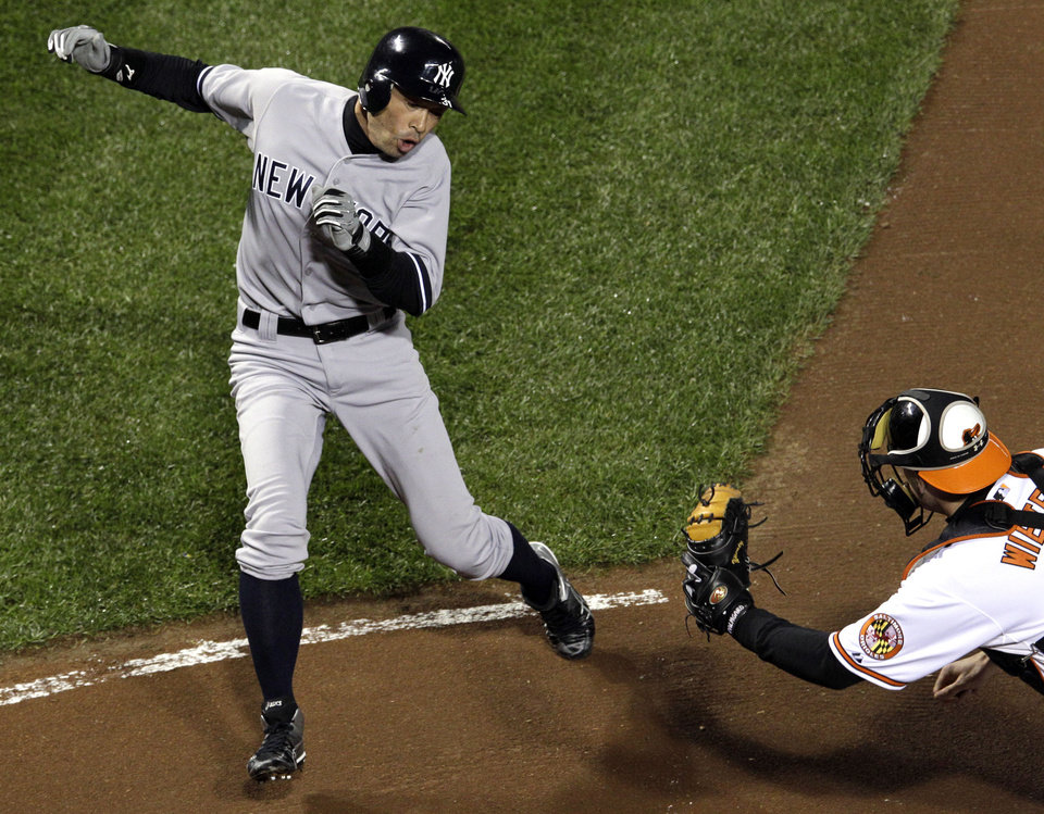 New York Yankees\' Ichiro Suzuki, left, of Japan, runs past Baltimore Orioles catcher Matt Wieters to score a run on a double by Robinson Cano in the first inning of Game 2 of the American League division baseball series on Monday, Oct. 8, 2012, in Baltimore. (AP Photo/Patrick Semansky)