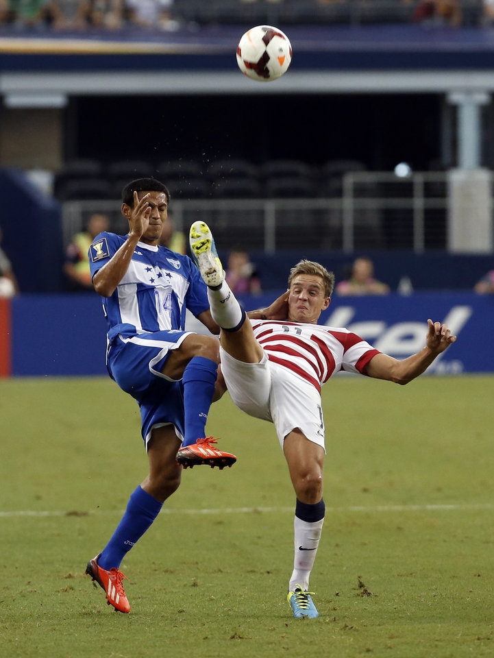 Photo - Honduras' Andy Najar (14) and United States'  Stuart Holden (11) battle for control of the ball during the first half of the Gold Cup semifinals at Cowboys Stadium, Wednesday, July 24, 2013, in Arlington, Texas. (AP Photo/Brandon Wade)