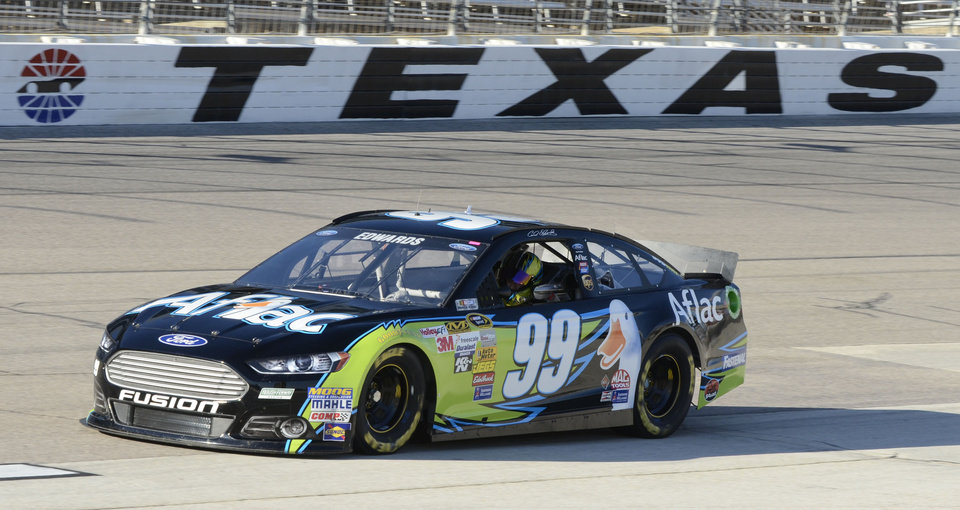 Photo - Driver Carl Edwards (99) drives his car onto pit row after qualifying Sunday's NASCAR Sprint Cup series auto race at the Texas Motor Speedway, Friday, Nov. 1, 2013, in Fort Worth, Texas. Edwards qualified on the pole. (AP Photo/Larry Papke)